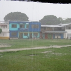 Kids playing fútbol in the Capurganá «square» under a heavy rain