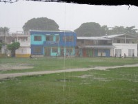 Kids playing fútbol in the Capurganá «square» under a heavy rain