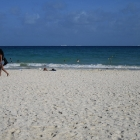 White sand, blue water, beautiful girls passing by …